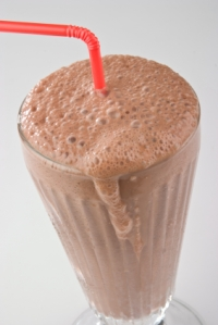 chocolate milkshake in a glass with red straw
